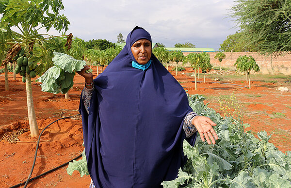 Habiba poses for pictures with leafy greens on her farm