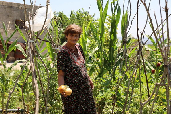 Radha picks vegetables from her farm as part of the project.
