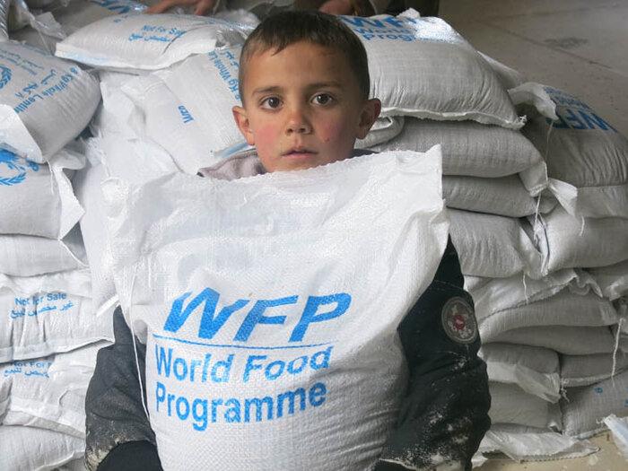 petit garçon avec un sac de vivres du WFP