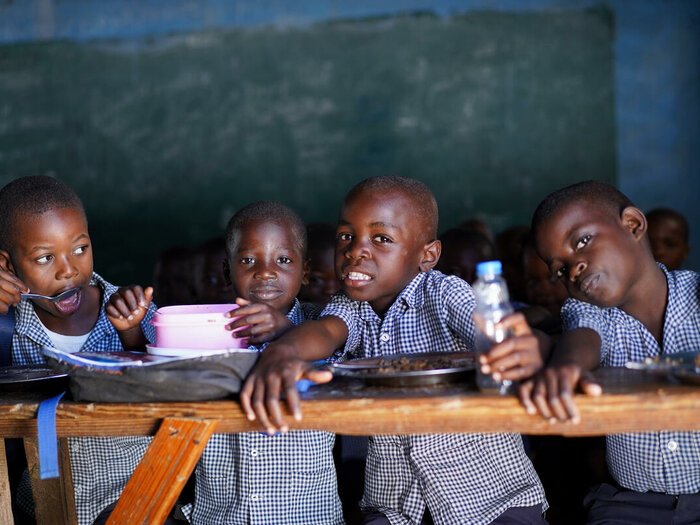 four kids are sitting in their classroom